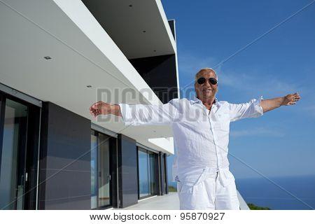 senior man in front of luxury modern home villa