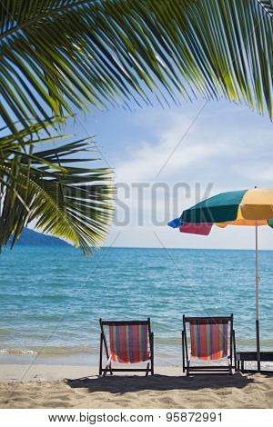 two sun-chairs and parasol at a tropical beach in Thailand