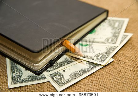 Notebook, Pencil And Money On The Old Tissue