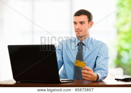 Portrait of a man using a credit card for online shopping