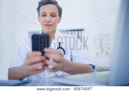 Happy doctor using her smartphone in medical office