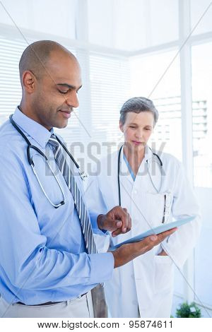 Concentrated medical colleagues working with tablet computer in the hospital