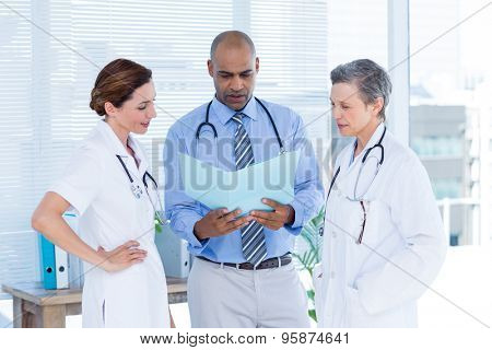 Concentrated medical colleagues analyzing file together in the hospital