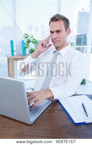 Attentive businessman talking on the phone in the office