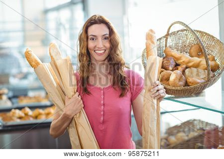 Pretty brunette holding baguettes at the bakery