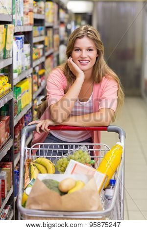 Portrait of a smiling pretty blonde woman in aisle in supermarket