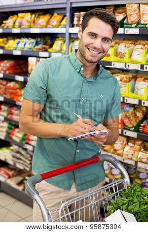 Portrait of smiling man writing on his notepad in aisle at supermarket