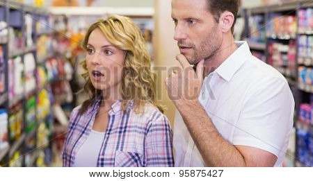 Casual couple looking at shelf in supermarket