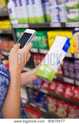 Woman comparing the price of a carton of with her phone at the supermarket
