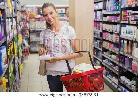 Woman taking a rice bag in the shelf of aisle at supermarket