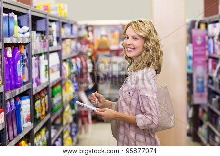 Portrait of a smiling pretty blonde woman writing on a notepad in supermarket