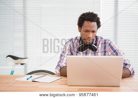 Young businessman looks confused at his laptop in the office