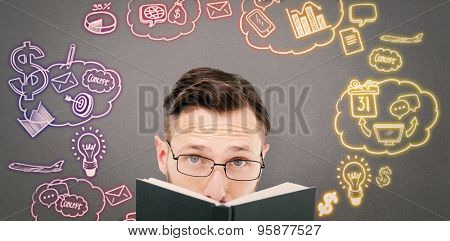 Young geek looking over black book against grey background