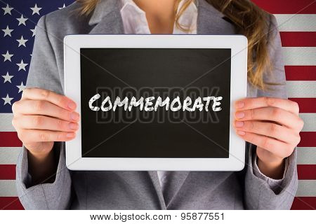 Businesswoman showing tablet against commemorate