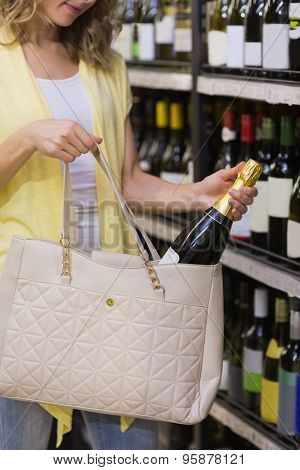 Pretty woman putting a chmpagne bottle in her bag in supermarket