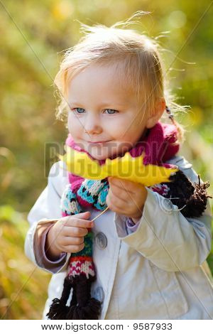 Toddler Girl Outdoors At Autumn Day