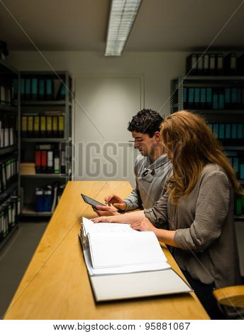 digitalization: young man and woman in the company archives