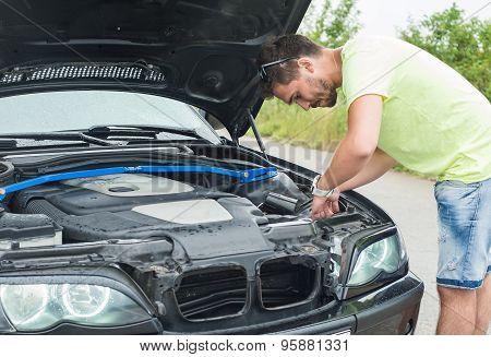 Man repairing a broken car by the road
