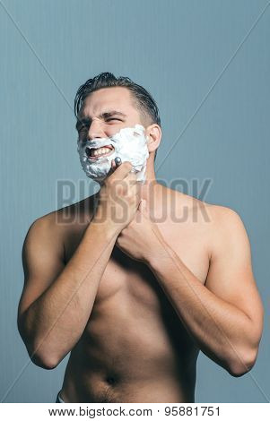 Young man shaving with hate and aggression