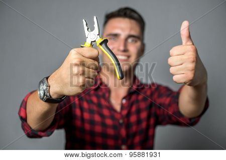 Young man holding pliers over gray background
