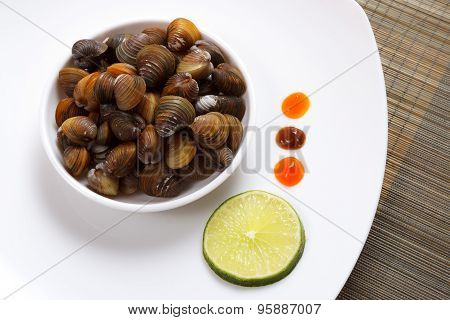 A Plate With Uncooked Mussels And Lime With Sauces On A Brown Mat