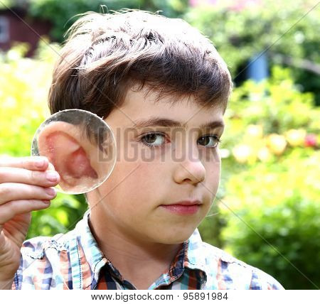 Teen Boy Magnify His Ear With Lense On The Summer Background