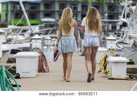 Two teenage sisters walk down a pier