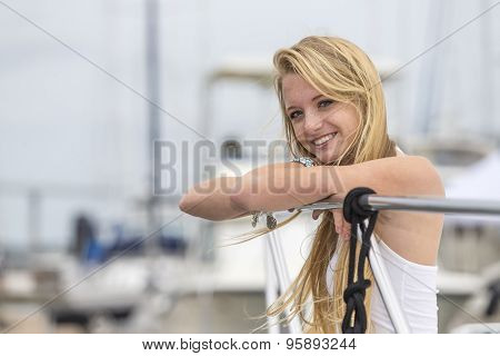 A teenage blonde model posing outdoors with boats