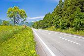 stock photo of plateau  - Roadway in the fresh green plateau under blue sky - JPG