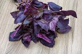 foto of basil leaves  - Fresh violet Basil leaves heap on the wood background - JPG