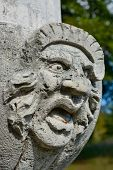 image of ugly  - Ugly face sculpture grimacing on stone wall - JPG