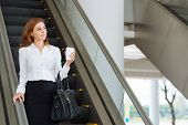 stock photo of escalator  - Dreamy businesswoman going down the escalator in office building - JPG