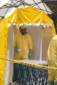 stock photo of decontamination  - a hazmat crew member awaiting a victim in a decontamination shower - JPG