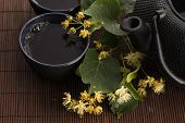 foto of teapot  - teapot and cup with linden tea and flowers - JPG