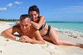 image of crystal clear  - Happy loving couple on a beautiful deserted beach with turquoise and crystal clear waters of the Caribbean sea in the Dominican Republic on the island of Saonna - JPG