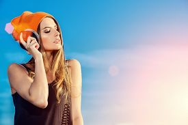 picture of rap-girl  - Modern young woman listening to music on headphones outdoor - JPG