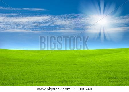 Blue sky and green field with sun effect