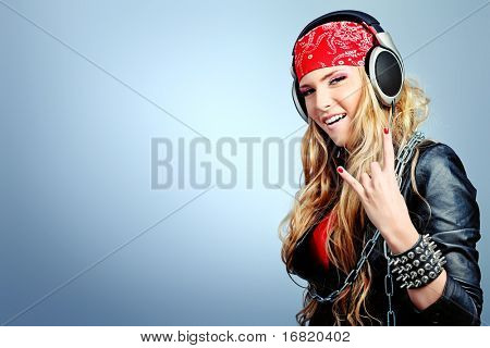 Portrait of happy girl listening a music in headphones. Studio shot over grey background.