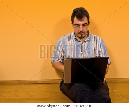 young man sit down on bamboo floor work with his laptop 02