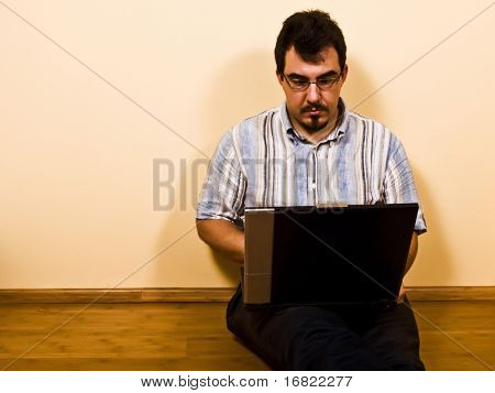 young man sit down on bamboo floor work with his laptop 01