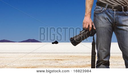 detail of photographer and desert landscape background