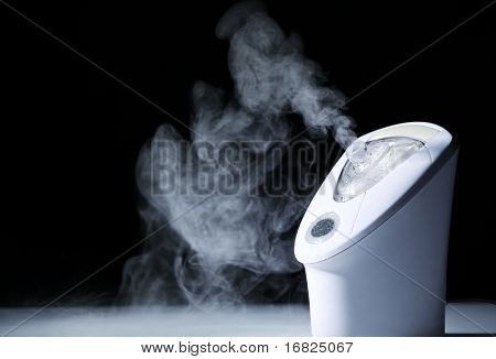 closeup image on aerosol machine in action on dark background