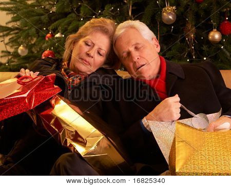 Tired Senior Couple Returning After Christmas Shopping Trip