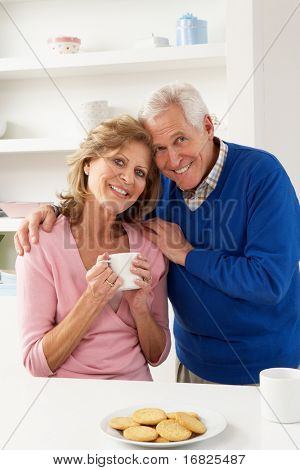 Senior Couple Enjoying Hot Drink In Kitchen