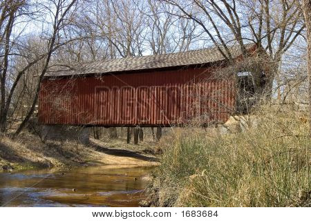 Red Wooden Covered Bridge Over A Stream