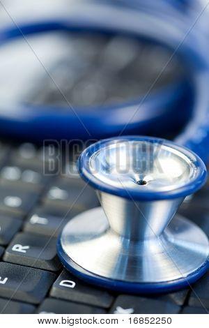 Blaue Stethoskop in der Mitte der Tastatur