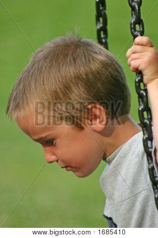 Boy Serious On Swing