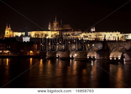 Prague castle and charles bridge at night.