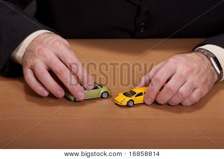 Businessman playing with his dream cars