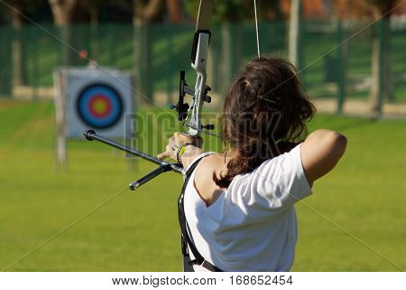 Back of archery athlete aiming at a target in the distance